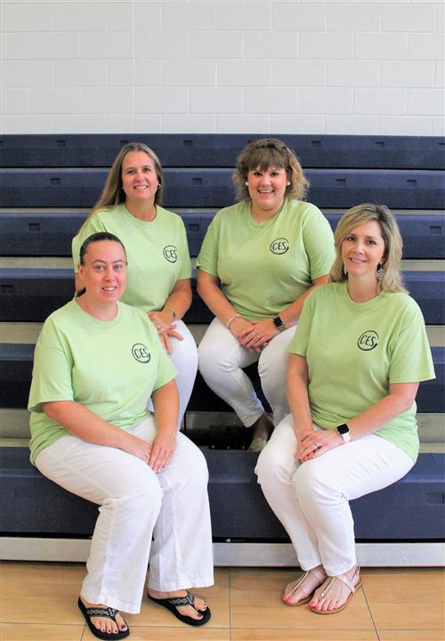 Four female teachers sitting together on bleachers