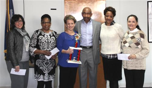 Fitness Zone Owner and Manager George Gibson (middle) presents principals of area schools with chec